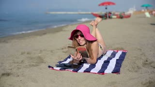 Young woman in hat reading book on the beach