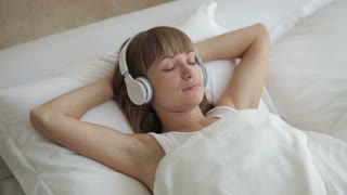 Young woman in headphones lying in bed and smiling