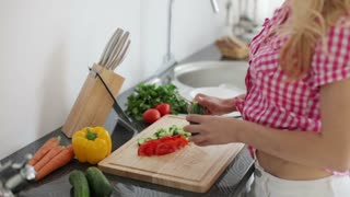 Young woman in kitchen chopping vegetables