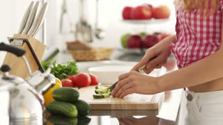 Young woman in kitchen cutting vegetables on cutting board