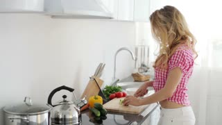 Young woman in kitchen cutting vegetables with smile
