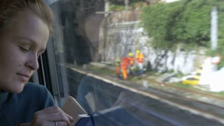 Young woman in moving train making sketches or taking notes in her pocket-book. When thinking, she looking out the window