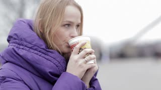 Young woman in purple jacket eating fast food and drinking hot tea outddor in cold weather.