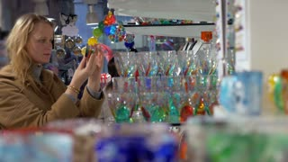 Young woman in the shop of Venetian glass. She examining different glasses decorated with colorful ornate patterns