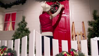 Young woman is decorating the front door of the house with a fur wreath on a christmas eve night. Christmas colors. Slow motion. dolly shot.