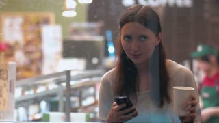 Young woman is sitting in coffee shop, drinking coffee and texting to friends using smartphone. Shot is made through the show window.