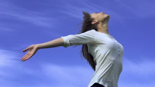 Young woman is standing with her arms open to the wind, enjoying the breeze and the sun. Slow Motion 240 fps. HD 1920x1080. Spring or summer relaxation concept.