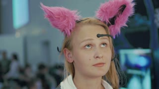 Young woman is trying on Brainwave Controlled Cat Ears and taking selfie. Ears are moving depending on her mood.