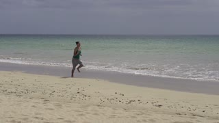 Young woman jogging on the beach, slow motion shot at 240fps