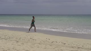 Young woman jogging on the beach, slow motion shot at 60fps