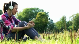 Young woman listen to music on her smartphone in the park