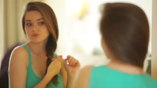 Young woman looking at camera and straightens hair