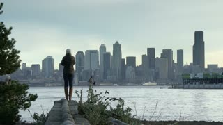 Young woman looks across water to downtown Seattle