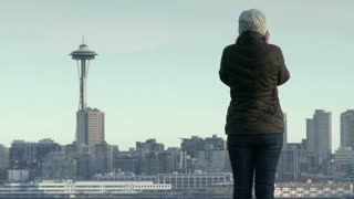 Young woman looks across water to Seattle space needle