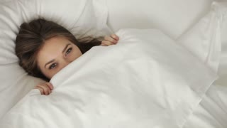 Young woman lying in bed pulling up blanket and smiling at camera. Panning camera