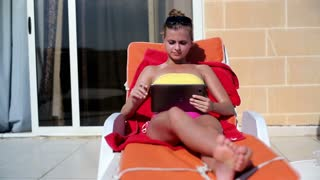 Young woman lying on sunbed and chatting with tablet computer