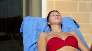 Young woman lying on sunbed and relaxing
