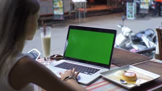 Young woman or girl student using a laptop outside and drinking coctail. Notebook with green screen.