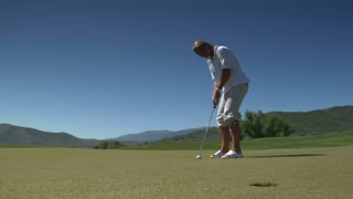 Young Woman Putts Golf Ball And Misses