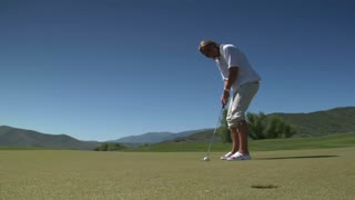 Young Woman Putts Golf Ball Into Hole