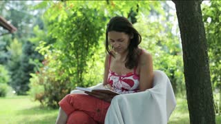 young woman reading a book in the garden