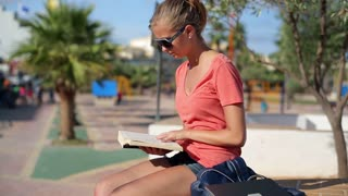 Young woman reading book in the park, steadycam shot