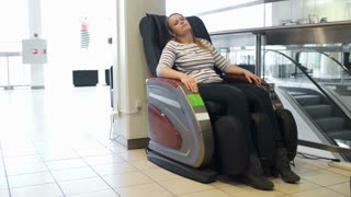 Young woman relaxing and getting pleasure in massage armchair in shopping center