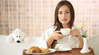 Young woman relaxing in bed drinking tea looking at camera and smiling