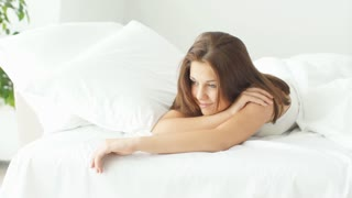 Young woman relaxing in bed smiling and laughing at camera