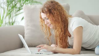 Young woman relaxing on sofa using laptop and smiling