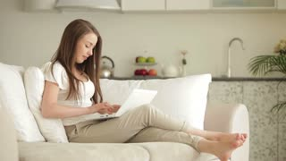 Young woman relaxing on sofa with laptop closing it and smiling