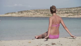 Young woman relaxing on the beach, slow motion shot at 240fps