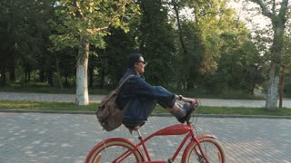 Young woman riding vintage bike in park and having some fun, slow motion