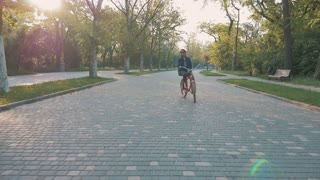 Young woman riding vintage bike in park and smiling, slow motion