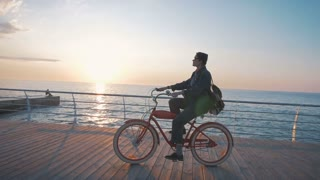 Young woman riding vintage bike on seafront during beautiful sunrise.slow motion