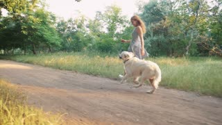 Young woman running with retriever dog in park during sunset, slow moion