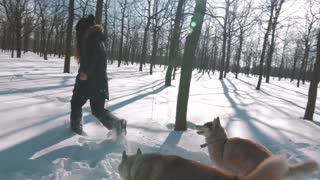 Young woman running with siberian husky dogs in show forest, slow motion