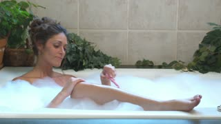 Young Woman Shaving in Legs in Bath 3