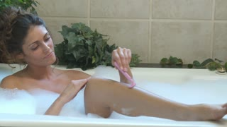 Young Woman Shaving in Legs in Bath 6
