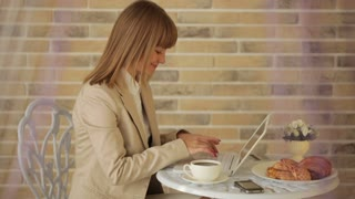 Young woman sitting at cafe using laptop and drinking coffee