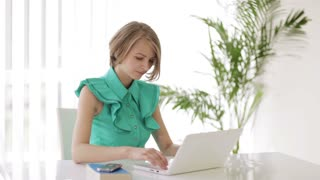 Young woman sitting at desk using laptop looking at camera and smiling. Panning camera