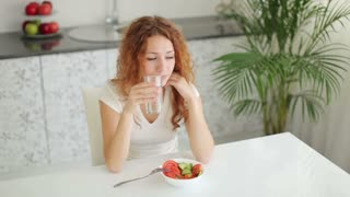 Young woman sitting at kitchen table drinking water and smiling at camera