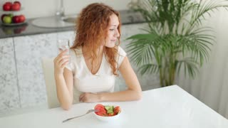 Young woman sitting at kitchen table with bowl of salad in front of her and drinking water with smile