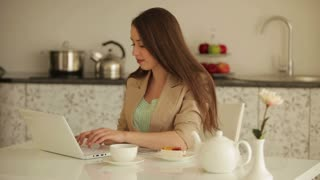 Young woman sitting at table using laptop drinking tea and eating cake time-lapse
