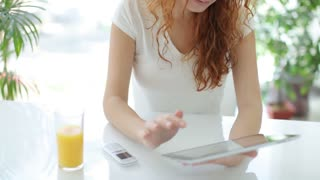 Young woman sitting at table using touchpad and smiling at camera