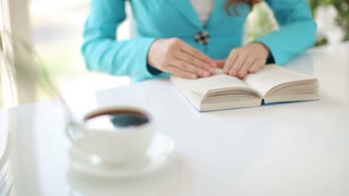 Young woman sitting at table with book and cup of coffee