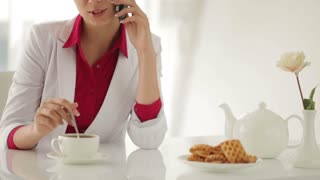 Young woman sitting at table with cup of tea and talking on cellphone
