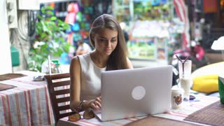 Young woman sitting at the table and using laptop outdoors