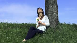 Young woman sitting by the tree and smelling yellow flower outdoors. Slow Motion 240 fps. HD 1920x1080. Spring or summer relaxation concept.