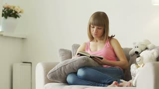 Young woman sitting in living room and reading book